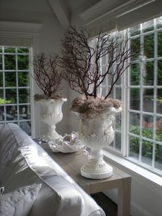 .Tree branches with peat moss and white urns.... for mantle?? Would be fun to change them for the season.