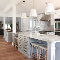 Garage space turned Expansive kitchen, this gorgeous space features two islands! A seamless quartz and a butcher block. Two toned cabinets with a slight variation in color provides depth and dimension without being over bearing. #kitchen #kitchendesign #kitchenremodel #kitchenideas #transitionalkitchen #transitionaldesign