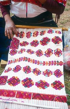 A weaver from Tenejapa Chiapas proudly shows the beautiful weaving on her backstrap loom