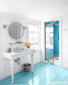 In the shower of a New England farmhouse designed by architect Nate McBride and interior designer Kari McCabe, sandblasted wall tiles were chosen to evoke sea glass. The wood floor is painted in Tidewater by Sherwin-Williams. Click through for more of the best bathroom colors and paint color schemes for bathrooms.