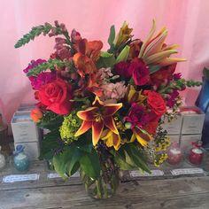Green Hydrangea, Hot pink mini carns, Orange alstromeria, Lavender Snap Dragons, Orange Roses, Light pink Stock, Purple Seeded Eucalyptus, Yellow and Red Lilies