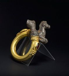Ring in the form of a Hippocampus: Gold and silver with two garnet gemstones, cut en cabochon. Hellenistic, 3rd - 2nd Century BC.