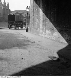 A covered horse-drawn cart belonging to the LMS railway company passes a gas lamp on a street corner. Place: Greater London Date 1945 - 1950 Photographer: John Gay Greater London, Coal Mining, Horse Drawn, Photographers, Cart, Corner, England, Street, Places