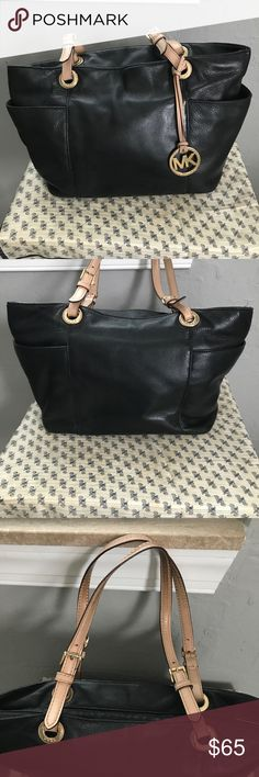 """Michael Kors jet set top zip tote Black leather tote with tan leather straps with buckles. Gold interior with four open pockets and one zippered pocket as well as one pocket on each side of the exterior of the bag. Minor marks on the front and back with very minor fraying on the top of the bag. The leather also has some darker areas on the straps. Measures 17"""" across, 10"""" top to bottom, and 9 1/2"""" from height of straps to top of bag. Michael Kors Bags Totes"""
