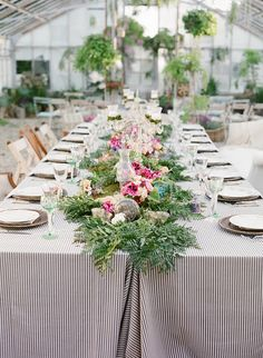 Two long tables pushed together. Striped table cloth and beautiful elongated center piece.