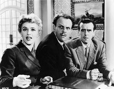 Jill Adams, Terry-Thomas and George Cole causing havoc at the front desk of the Green Man hotel in Newcliff where they believe Alastair Sim's hitman Harry Hawkins has planted a bomb for the benefit of pompous, philandering MP Sir Gregory Upshott (Raymond Huntley). The Green Man (1956)
