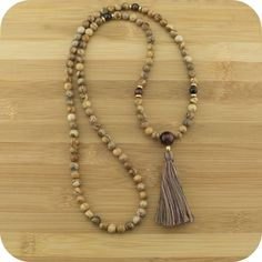 Description This premium quality full length mala beads necklace features wood jasper with red tigers eye markers & guru bead, gold plated brass accents and a 100% cotton multi color tassel. The nurturing nature of Jasper helps to support and sustain us during difficult and stressful times. It is known to offer protection and absorb all types of negative energy. It is commonly used in healing and is useful in unifying and bringing balance to all aspects of our life. Red tigers eye may help…