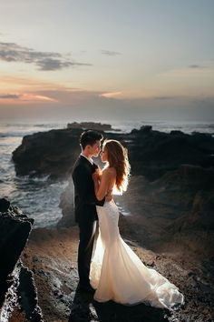 Glowing couple in classic black suit and white mermaid wedding gown embrace atop rocky cliffs with foamy waves crashing ashore // Following their dramatic ballroom wedding and gritty day-after-wedding photo shoot, Joshua and Cheryl are back to steam up our screens with a pre-wedding in Bali captured by Gustu of Maxtu Photography. Whether at a volcano, lake, waterfall, beach or cliffs, the connection Joshua and Cheryl share is palpable. {Facebook and Instagram: The Wedding Scoop}
