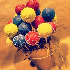 red, blue and yellow cake pops in a fun bucket bouquet. www.cakeballers.com #thecakeballers #cakeballers #cakeballer #cakepops #bouquet