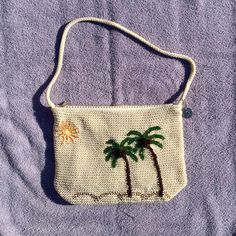 "NWOT Sak Palm Tree Handbag NWOT and never used. Beaded palm trees and sun create this perfect for Summer beach scene. 12"" x 8"", 12"" drop and 3""x9"" footprint, zippered pocket on outside, one zippered and three open pockets inside. The background is cream and perfectly clean. Sak Bags Shoulder Bags"