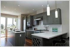 White countertop, grey cabinets, dark hardwood floors