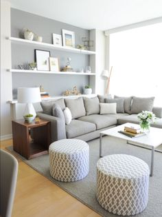 Clean lines in this crisp gray and white room. Wall shelfs and round patterned ottomans pull it all together.
