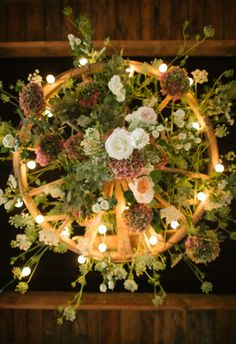 Underside view of wagon wheel chandelier. Use mason jars instead and hops, grapevine, barbed wire, twine, other greenery?