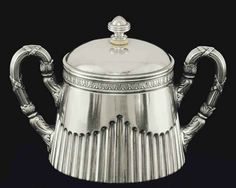 A Silver Sugar Bowl   Marked K. Fabergé with the Imperial warrant, Moscow, 1908-1917   Of tapering form, the lower section fluted, the rim with band of stiff leaves, the hinged cover with reeded finial and ivory insulator, with leaf-clad ribbon-tied reeded handles, the interior gilt, marked under base and inside cover  4 7/8 in. (12.4 cm.) high   17½ oz. (543 gr.) gross weight