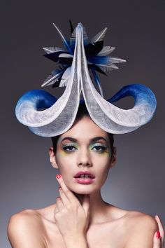 Elizabeth (view 1) | Label: Lisa Tan Millinery | Spring/Summer 2014 | Hand-sculpted ombré-dyed sinamay twists set on a sinamay base, encircling an ombré-dyed feather starburst. Shown in cobalt/white colour combination