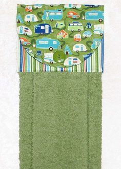 A green hand towel with cheerful campers and stripes. The plush green towel is more luxurious than a standard kitchen towel. Featuring a designer fabric of travel trailers on green and a coordinating green stripe fabric, it is sure to add fun to your home or camper kitchen and bath.  This handmade hanging towel works well buttoned over the handle of stove or dishwasher. It can even be used over a towel bar in the bathroom or powder room.  6 x 17 when hanging. The front of this hanging towel…