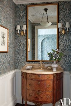 In a powder room, the ceiling fixture and sconces are from Remains Lighting, and the Twigs wallpaper is from John Rosselli & Assoc | archdigest.com