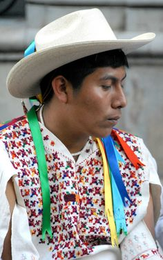 """This young man (wearing the traditional clothing and hat of his Mixtec community on the coast of Oaxaca) awaits his turn at an indigenous language """"poetry slam"""" in the city of Oaxaca"""