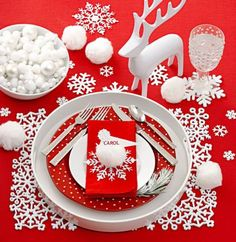"Use assorted-size paper, plastic or felt snowflakes as coasters or place mats. Or toss them across the table. Add ""snowballs"" to the mix with different-size pom-poms. Frosted white ornaments and pom-poms fill a bowl for a super simple centerpiece. Hot-glue a name card to a pom-pom attached to a snowflake base as a place card. The polka-dot plate and flatware inspired the falling snow motif (made with self-adhesive dots) on the water glass."