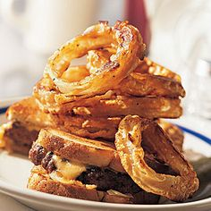 ONION RINGS 4 servings (serving size: 4 onion rings and 1 tablespoon ketchup) 400 2 large onions, peeled (about 1 1/2 pounds) 0.66 cup(s) all-purpose flour 0.5 teaspoon(s) salt 0.25 teaspoon(s) paprika 0.25 teaspoon(s) freshly ground black pepper 0.33 cup(s) flat beer 1 large egg white, lightly beaten 1.5 tablespoon(s) vegetable oil, divided Cooking spray 0.25 cup(s) ketchup  Preheat oven to 400 degrees. Cut the onion crosswise into 3/4-inch-thick slices, and separate into rings. Use 16 of the largest rings; reserve remaining onion for another use. Lightly spoon flour into a dry measuring cup; level with a knife. Combine flour, salt, paprika, and pepper in a medium bowl. Stir in beer and egg white (batter will be thick). Heat 1 1/2 teaspoons oil in a large nonstick skillet over medium-high heat. Dip 5 onion rings in batter, letting excess drip off. Add onion rings to pan; cook for 2 minutes on each side or until golden. Place the onion rings on a jelly-roll pan. Repeat procedure of dipping onion rings in batter and cooking in remaining oil, ending with 6 rings. Coat the onion rings with cooking spray. Bake at 400 degrees for 10 minutes or until crisp. Serve rings with ketchup.
