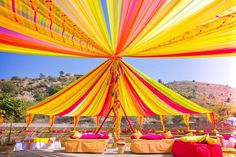 Colorful drapes tied in a canopy style with fuchsia and lime yellow bolsters and gadda for an outdoor day event