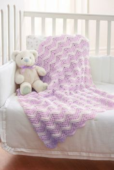"Chevron Lilac & White Crochet Baby Blanket This adorable baby blanket is the perfect gift for a newborn, made from Loops & Threads Snuggly Wuggly, it will be soft on baby's skin while keeping them warm. Materials: Loops & Threads Snuggly Wuggly (Solids 140 g/5 oz): Main Color (MC) (Soft Lilac) 2 balls, Contrast A (White) 1 ball, Size H/8/5mm Crochet Hook Measurements: Approx 33"" x 37"""