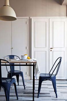 Comedor simple y claro con acentos en azul y gris en una oficina convertida en departamento, en el microcentro porteño.