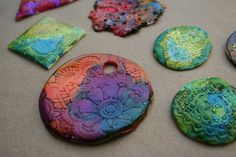 """First we rolled out some white polymer clay   (Sculpey or Fimo from the craft store) and   rolled paper doilies into the clay to create lacy impressions.  The next day, """"E"""" (age 8.5) and I used my Adirondak brand alcohol inks  to dye the ornaments. This wasn't a project for her little sister """"C"""" (age 4.)      They're messy and they stain everything,  """"E"""" had the genius idea for us to wear surgical gloves."""
