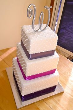 3 tiered square wedding cake with purple ribbons and a monogram topper <3