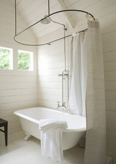 white claw foot tub with stunning windows, planked walls and a center shower head.