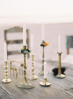 a collection of #gold candlesticks decorating the table #bohemian | Photography by kurtboomerphoto.com, Event Design and Planning by http://www.jillandcoevents.com   Read more - http://www.stylemepretty.com/2013/08/29/summerland-photo-shoot-from-jill-and-co-events/