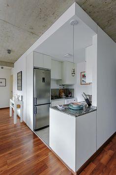 Cocina comedor integrada en una puesta clásica y tonos claros. La cocina, delimitada como un cubo blanco.