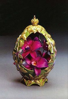 The Orchid Egg, a creation by Theo Fabergé of his favorite flower, is crafted in fine porcelain and adorned with delicately hand painted exotic birds and butterflies resting in the foliage. Looking into the Egg, there is a beautiful cluster of brilliantly coloured orchids, intricately crafted in fine bone china. The Egg is offset with the Imperial Russian Crown with a cabochon ruby.