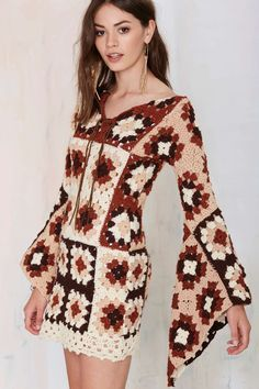 This vintage dress is brown, beige, and off-white, and features semi sheer crochet knit design, bell sleeves, and v-neckline with leather tie closure.