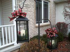 Hang lanterns from shepherds hooks during the holiday season.