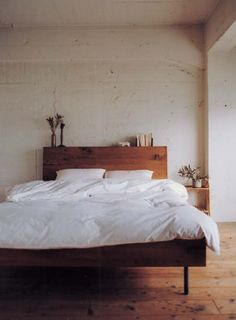 simple white bedroom - white duvet, a small plant and an organic modern wood bed