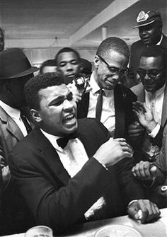 Boxer Muhammad Ali (L) having a laugh with activist Malcolm X (C, glasses) at the Hampton House shortly after gaining the heavyweight boxing championship.