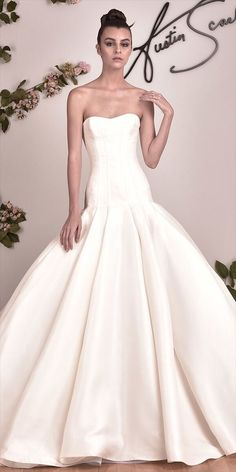 Strapless dropped waist ballgown. Vertically seamed bodice flows into voluminous fluted skirt.
