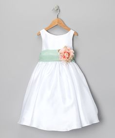 Just a quick zip up the back and a girl will look her most fabulous in this endearing dress. A sash-embellished waist with a big, blooming rose and prim pleats make this pretty piece shine on any occasion.
