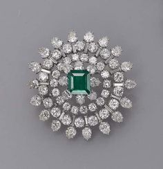 AN EMERALD AND DIAMOND BROOCH/PENDANT, BY HARRY WINSTON   The square-shaped emerald weighing 2.82 carats to the brilliant-cut and pear-shaped diamond sunburst surround, 4.5 cm diameter  With maker's mark of Jacques Timey for Harry Winston