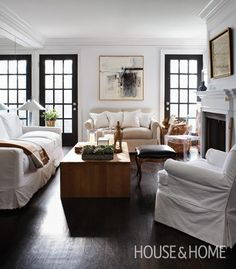 Designer Michael Angus painted the two inexpensive builder doors at the end of his living room black, making them look like vintage metal. A master of the mix, he paired a contemporary teak coffee table with an antique leather stool and slipcovered furniture. The focal point of the room is a simple fireplace which Michael installed to give the sense of being in a house, rather than an apartment.