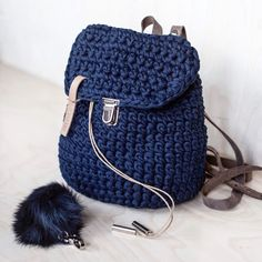 This tiny navy backpack is a custom order. It is made of ♻️recycled t-shirt yarn with leather bands sand color. It's smaller than my basic backpacks and it has this cute fur pom-pom trinket attached. You can always ask for customization in my shop!