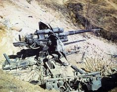 Colour photo of an abandoned German 88mm flak gun.