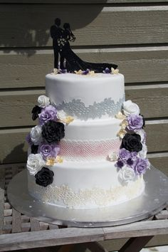 Three-tiered wedding cake with flowers and edible lace
