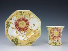 Een eierschaal porseleinen kop en schotel, model 137 en 141. Beschilderd met spinchrysanten in de kleuren rood, oranje, geel , groen en lila. Kop en schotel zijn gemerkt met het schildersignatuur van Sam Schellink én dat van Hendrika Kromi, werkorder nummer 243, jaar 1906. Het kopje is 5,7 cm hoog en het schoteltje is 11,4 cm in doorsnede. Beschilderd in april 1906 door Hendrika Laurie ( 20 jaar), Josphina Bordat (19 jaar) en Hendrika Kromi (16 jaar).
