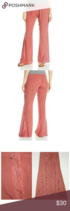 O'Neill Dusty Rose Woven/Lace Pants These soft wide leg pants from O'Neill are the perfect piece for a sunny weekend afternoon. They are light and super comfortable with an elastic waistband. The beautiful lace design down the side is straight from waist to knee then flares out under the knee. The fabric is 100% viscose. O'Neill Pants Wide Leg