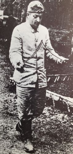 This is a picture taken of a Russian Soldier supposedly using the dowsing rod for whatever purpose.  Russia was a very strong believer in metaphysics and said this method could be used to find water, determine where to set up a camp, find a lost artifact, or, as part of a very long tradition, to determine where to best to place your largest cannon before battle for good luck (a tradition started in the 1500s.)