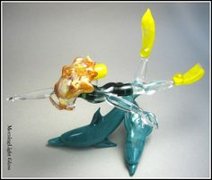 A single blonde haired girl in an underwater adventure meets up with a  couple of dolphins and swims along with them for awhile. I created her  using flamework/lampwork glass techniques. She is made fro Solid Boro  Rods. Her wet suit is a blue/ ivy green color.. fins and tank a bright  sunny yellow.Her dolphin companions are made from aqua glass.