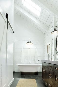 All white with sleek modern tile on the floor, an element of dark wood somewhere, and white linens.