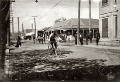 Boys on Bikes; Dallas, October 1913. Messenger boy in the heart of the Reservation (Red Light). Prostitutes run back and forth. Business beginning at mid-day. I saw messenger boys and delivery boys for drug stores from 15 years upward. Some still younger told me that they go there. This was in spite of a strong agitation being waged to close up the resorts. Photo and caption by Lewis Wickes Hine.